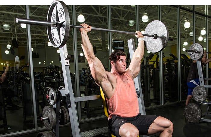 atleta a fazer o press de ombros com barra